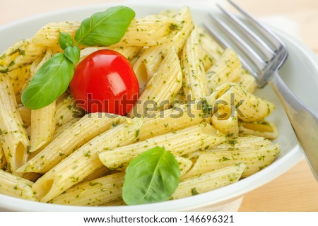 Pasta with basil pesto and tomatoes on wooden board