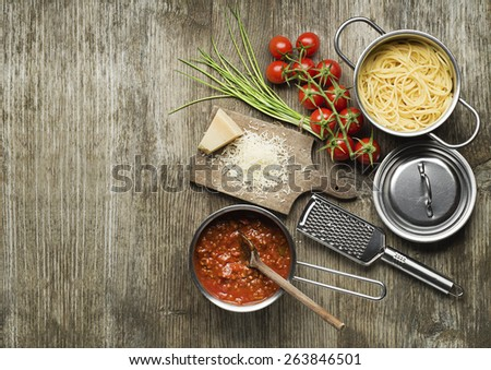 Pasta with bolognese sauce and parmesan cheese on wooden table - stock photo