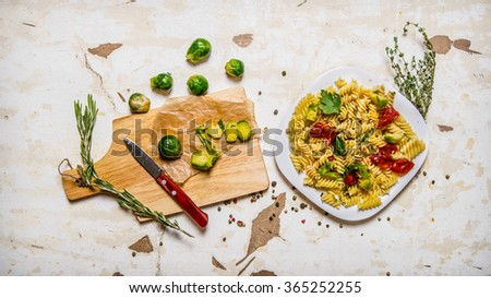 Pasta with Brussels sprouts, herbs and spices. On rustic background.  Top view - stock photo
