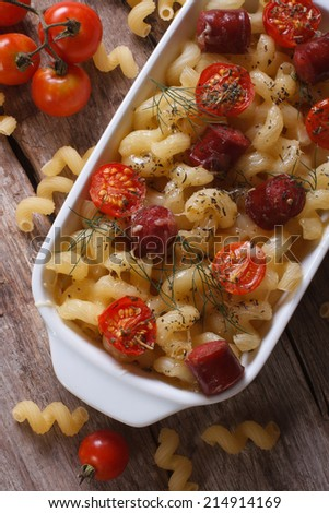 pasta with cherry tomatoes and sausages close-up view from above and ingredients. vertical  - stock photo