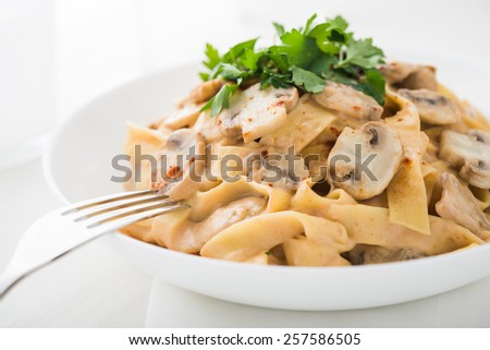 Pasta with creamy sauce, mushrooms and paprika close up. - stock photo