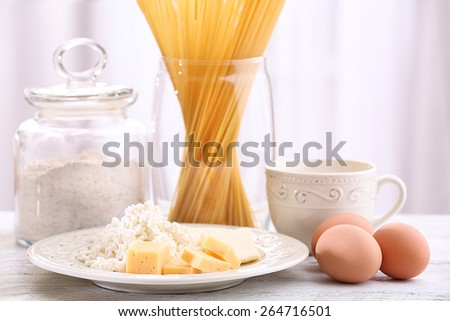Pasta with diary products, flour and eggs on wooden table on curtain background