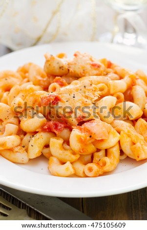 pasta with fish and tomato sauce on white plate on wooden background
