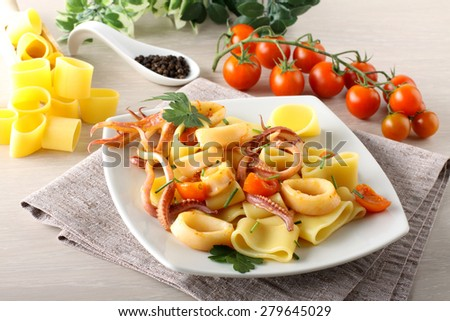 Pasta with fresh squid on complex background - stock photo