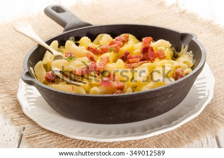 pasta with grilled bacon, thyme and melted cheese in a cast iron pan
