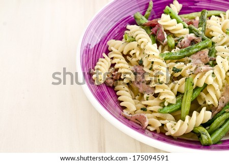 Pasta with ham and green beans in a purple dish. - stock photo