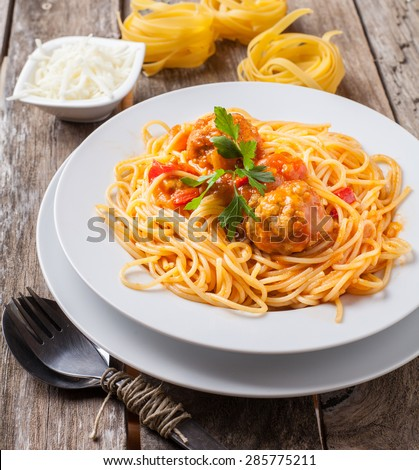 pasta with meatballs and parsley with tomato sauce on white plate - stock photo