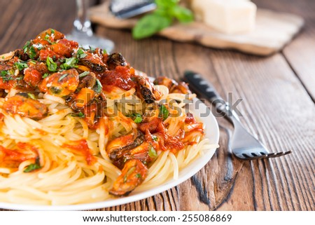 Pasta with Mussels and tomato sauce (on wooden background) - stock photo
