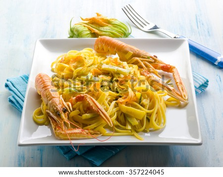 pasta with norway lobster zucchinis flower and saffron - stock photo