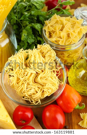 Pasta with oil, cheese and vegetables on wooden table close-up