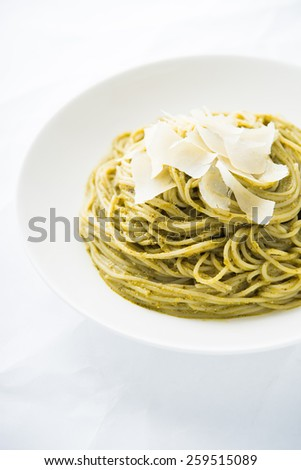 Pasta with pesto and parmesan on white background close up. Italian cuisine.