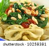 Pasta with pesto and spinach, cherry tomatoes and pine nuts. - stock photo