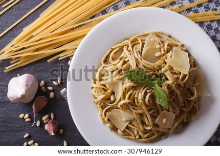 pasta with pesto, pine nuts and parmesan cheese on a plate and ingredients on the table close-up. horizontal top view - stock photo