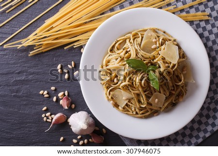 pasta with pesto, pine nuts and parmesan cheese on a plate and ingredients on the table. horizontal top view - stock photo