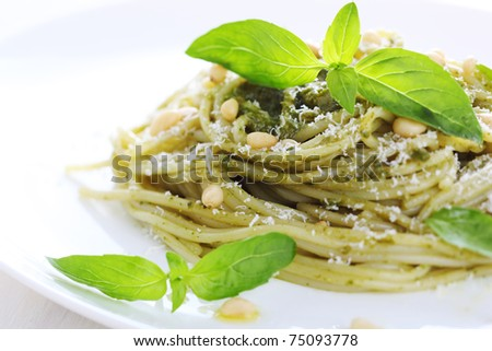 Pasta with pesto sauce, fresh basil and pine nuts on white plate - stock photo