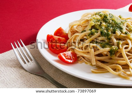 Pasta with pesto sauce on a top with cherry tomato decoration on red background - stock photo