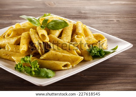 Pasta with pesto sauce, parmesan and vegetables - stock photo