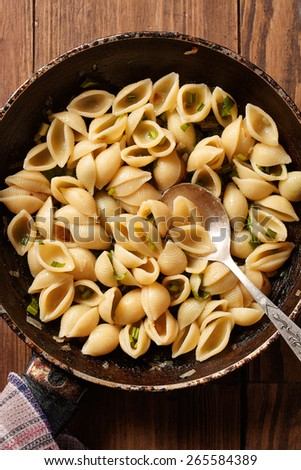 pasta with pieces of fried onions and spinach - stock photo