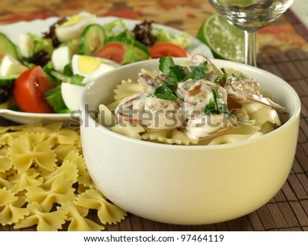 Pasta with prawns in a bowl,and  salad with eggs in the background.