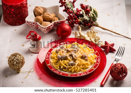 pasta with sausage cream sauce and nuts over christmas table