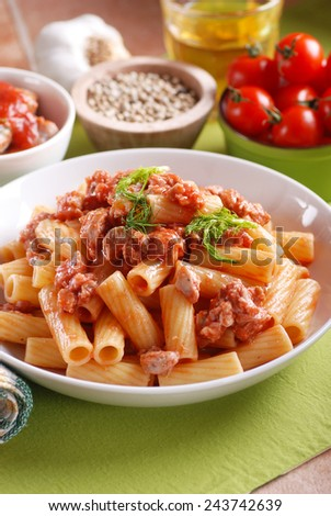 pasta with sausage sauce in the white dish