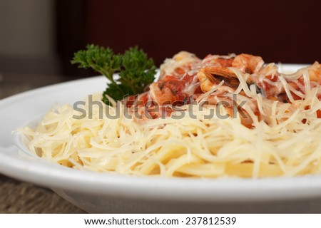 Pasta with seafood, greens and cheese - stock photo