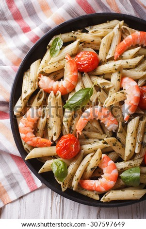 pasta with shrimp, tomato and pesto sauce on a plate close-up. vertical top view - stock photo