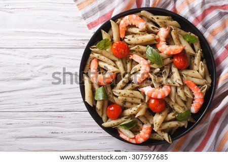 pasta with shrimp, tomato and pesto sauce on a plate.horizontal top view - stock photo