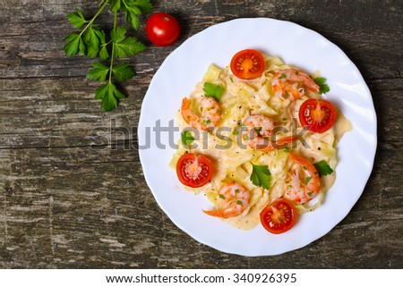 pasta with shrimp, tomatoes, herbs and cream sauce - stock photo