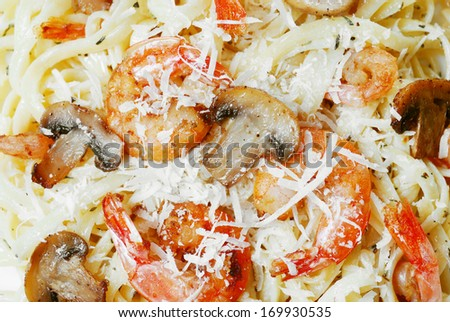 Pasta with shrimps, herbs and mushrooms on the wooden table