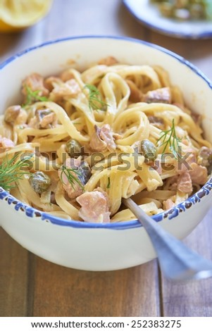 Pasta with smoked salmon and capers in cream sauce, italian cuisine - stock photo