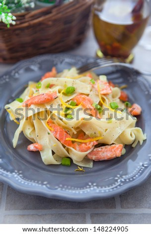 Pasta with smoked salmon and lemon zest on the gray plate on the stone table - stock photo