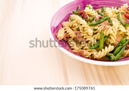 pasta with speck and green beans on a wooden table - stock photo