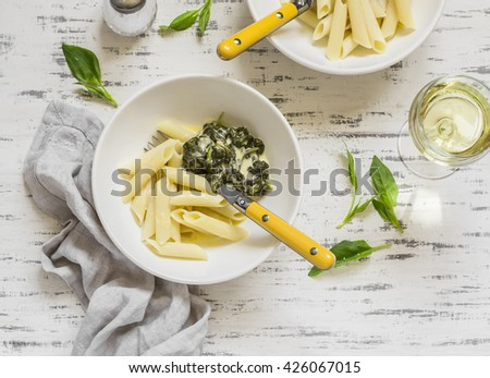 Pasta with spinach cream sauce and a glass of white wine on a light wooden background - stock photo
