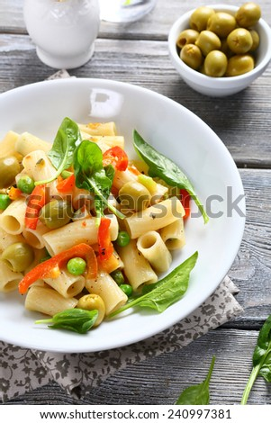 Pasta with spinach, peas and olives, food - stock photo