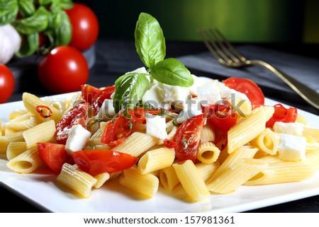 pasta with tomato and mozzarella green background - stock photo