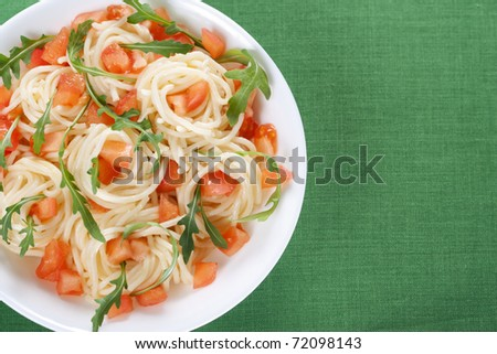 Pasta with tomato and rucola in bowl - stock photo