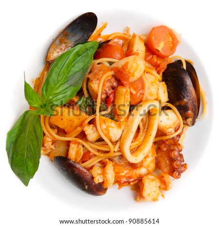 Pasta with tomato sauce, basil and seafood in plate