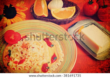 Pasta with tomato sauce,grated parmesan cheese,warm rolls of beef pastrami,grains of pumpkin, herbs and fresh tomato. Mediterranean food. Image done on textured background in vintage instagram style  - stock photo