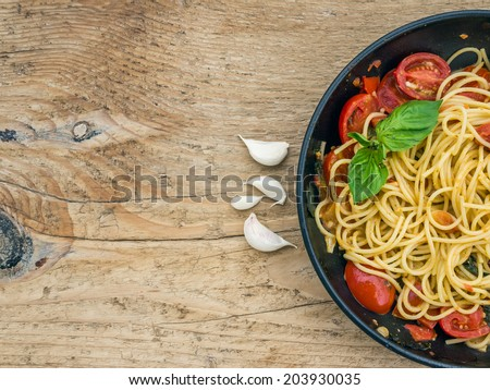 Pasta with tomatoes and basil on a wooden desk - stock photo
