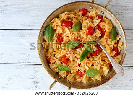 pasta with tomatoes and basil overhead on boards - stock photo