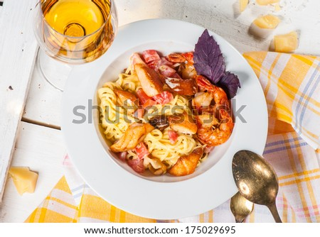 Pasta with tomatoes, big shrimps and cheese - stock photo