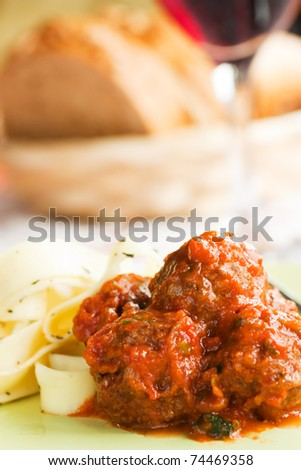 Pasta with tower aranged meatballs in tomato sauce. Focus is on the top meatball.