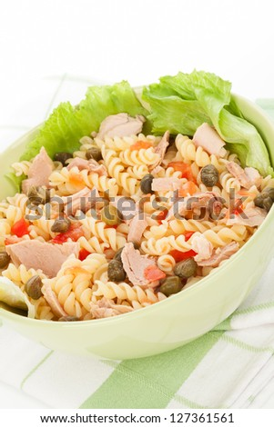 Pasta with tuna, capers, lettuce and vegetable in green bowl on white background. Culinary healthy eating. - stock photo