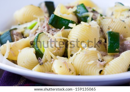 Pasta with tuna, zucchini, sauce and herbs on plate, delicious dinner - stock photo