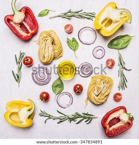 Pasta with vegetables around lie ingredients on wooden rustic background top view close up - stock photo