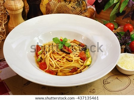 Pasta with vegetables: eggplant, zucchini, cherry tomatoes in white plate on the table - stock photo