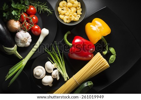 Pasta with Vegetables ingredients on black table - stock photo