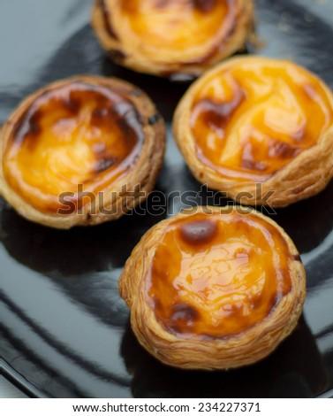Pasteis de nata on black plate - stock photo