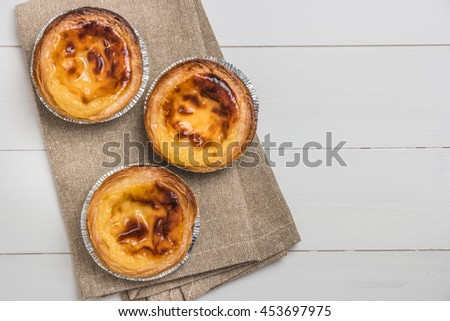 Pasteis de nata, typical Portuguese egg tart pastries on a set table. Top view with copy space - stock photo